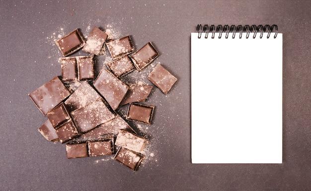 Vue de dessus chocolat recouvert de cacao avec carnet Photo gratuit