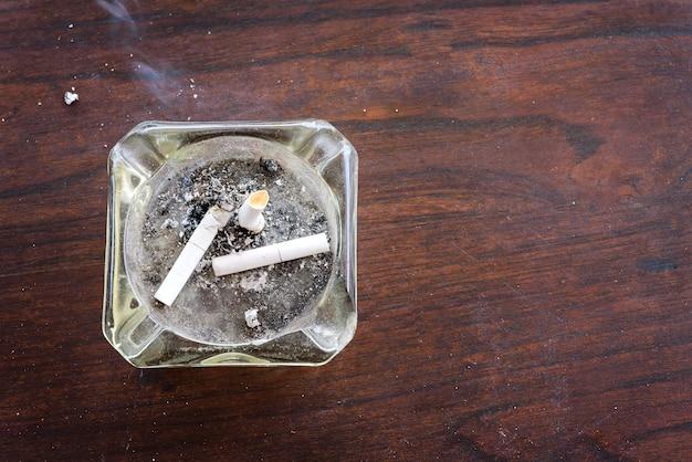 Vue de dessus de cigarettes bout à bout dans le cendrier sur une table en bois avec de la fumée de cigarette Photo Premium