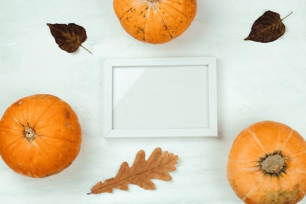 Vue de dessus de citrouille, feuilles d'automne et maquette cadre en bois blanc Photo Premium
