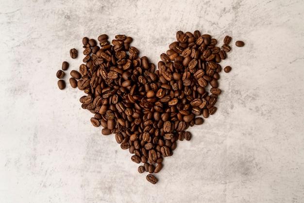 Vue de dessus coeur faite de grains de café torréfiés Photo gratuit