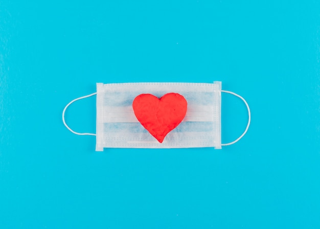 Vue De Dessus Coeur Sur Un Masque Médical. Horizontal Photo gratuit