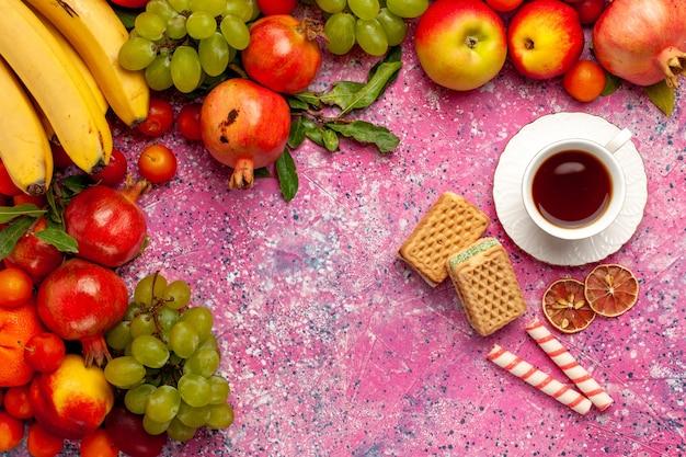 Vue De Dessus De La Composition De Fruits Frais Fruits Colorés Avec Du Thé Et Des Gaufres Sur Une Surface Rose Photo gratuit