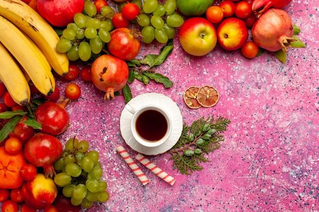 Vue De Dessus De La Composition De Fruits Frais Fruits Colorés Avec Tasse De Thé Sur La Surface Rose Photo gratuit