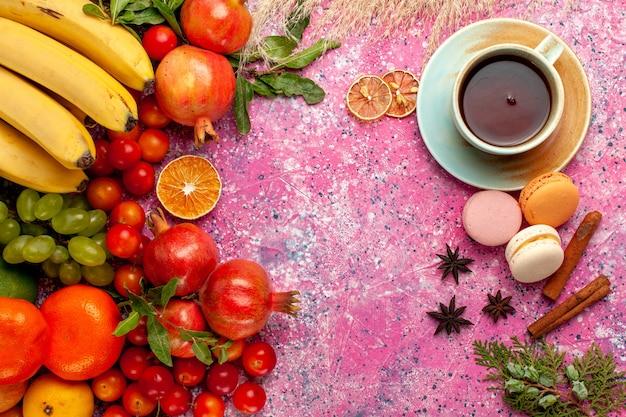 Vue De Dessus De La Composition De Fruits Frais Avec Une Tasse De Thé Sur Une Surface Rose Clair Photo gratuit