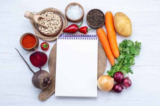 Vue De Dessus De La Composition Végétale Avec Des Légumes Frais Haricots Crus Carottes Bloc-notes Et Pommes De Terre Sur Le Bureau Blanc Salade De Légumes Repas Alimentaire Photo gratuit