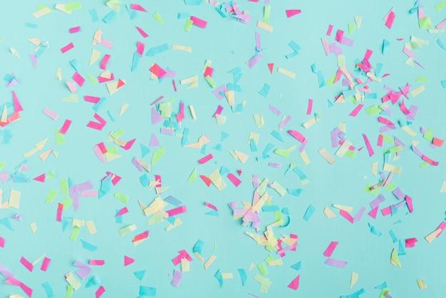 Vue de dessus de confettis multicolores sur fond turquoise Photo gratuit