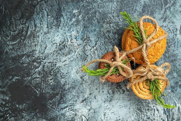 Vue De Dessus Cookies Attachés Avec Des Cordes Et Des Feuilles De Pin Sur L'espace De Copie De Surface Grise Photo gratuit