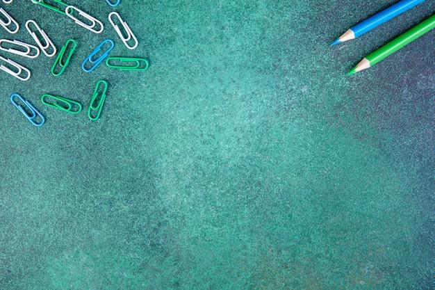 Vue De Dessus Copie Espace Blanc Trombones Vert Et Bleu Avec Des Crayons Bleu Et Vert Clair Sur Fond Vert Photo gratuit