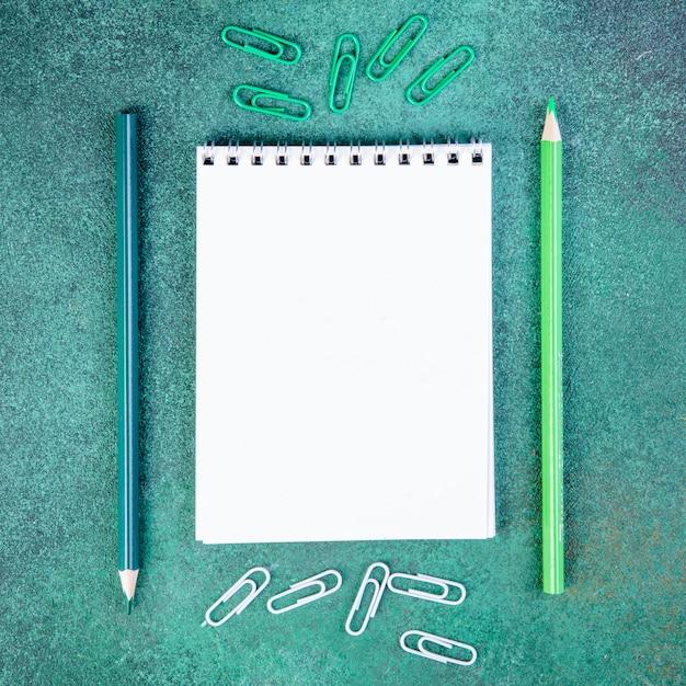 Vue De Dessus Copie Espace Crayons Vert Clair Et Bleu Avec Trombones Et Bloc-notes Sur Fond Vert Photo gratuit