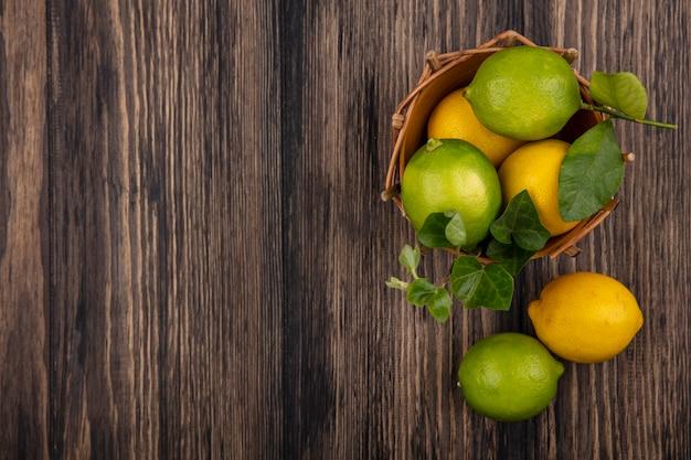 Vue De Dessus Copie Espace Limes Avec Des Citrons Dans Un Panier Sur Fond De Bois Photo gratuit