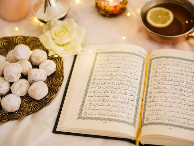 Vue De Dessus Coran Avec Thé Et Pâtisserie Photo gratuit