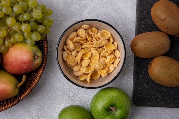 Vue De Dessus Des Cornflakes Dans Un Bol Avec Des Pommes Vertes Kiwi Poire Et Raisins Verts Sur Fond Blanc Photo gratuit