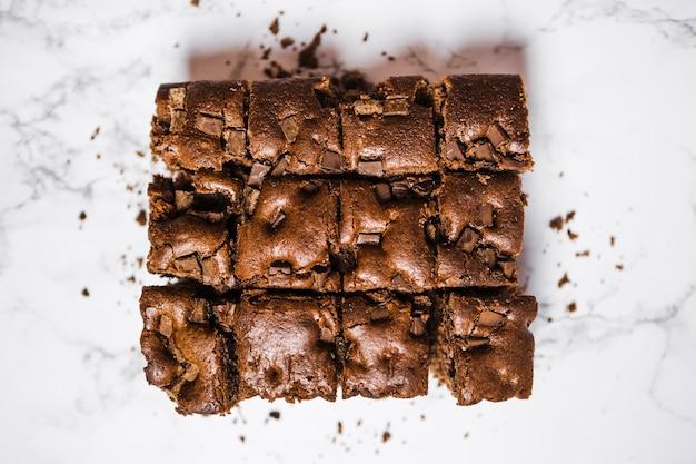 Vue de dessus coupe un gâteau au chocolat sur une table en marbre Photo gratuit