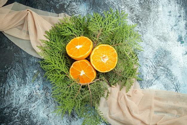 Vue De Dessus Couper Les Branches De Pin Oranges Sur Châle Beige Sur L'espace Libre De Surface Grise Photo gratuit