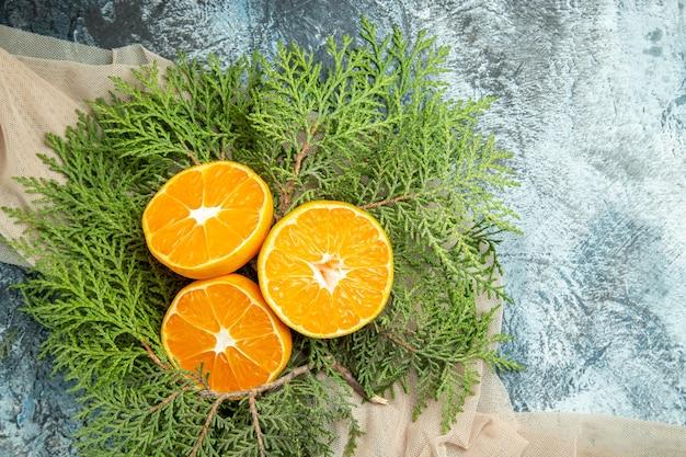 Vue De Dessus Couper Les Branches De Pin Oranges Sur Châle Beige Sur Surface Sombre Photo gratuit