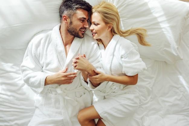 Vue De Dessus D'un Couple D'âge Moyen Amoureux En Peignoirs En Lune De Miel Couché Dans Un Lit Et Câlins. Photo Premium