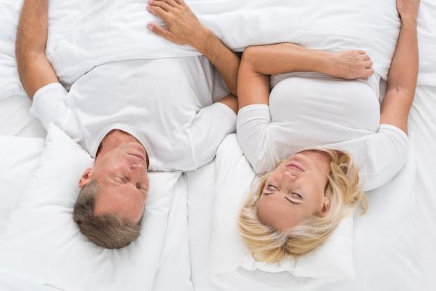 Vue De Dessus Couple Assis Dans Son Lit Photo gratuit