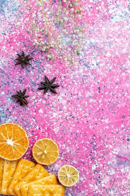 Vue De Dessus Des Craquelins Salés Au Citron Sur Un Bureau Rose Photo gratuit