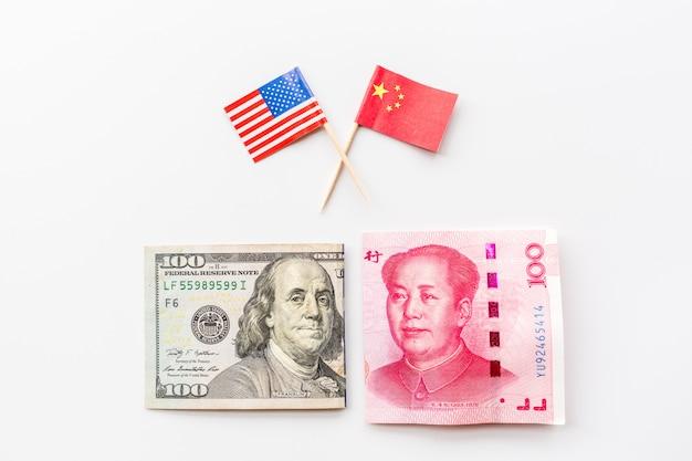 Vue de dessus créative à plat de drapeau de la chine et des états-unis et de l'argent comptant dollar américain et les factures de yuan chinois Photo Premium