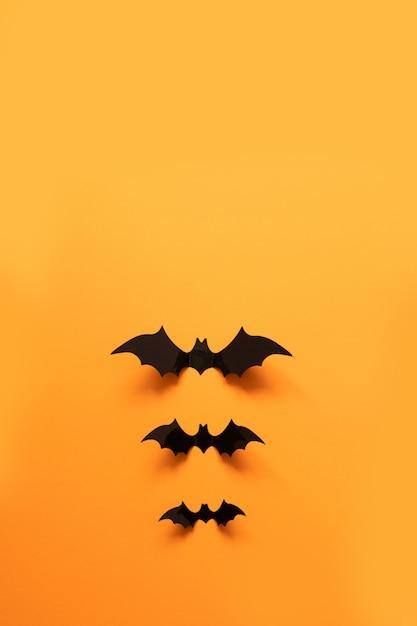 Vue de dessus créative plat poser automne composition d'halloween de chauves-souris en papier noir voler vers le haut Photo Premium