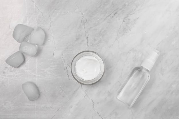 Vue de dessus de crème et bouteille sur fond de marbre Photo gratuit