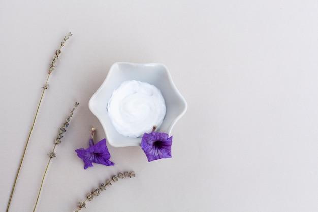 Vue de dessus de la crème pour le corps et de la lavande sur fond uni Photo gratuit