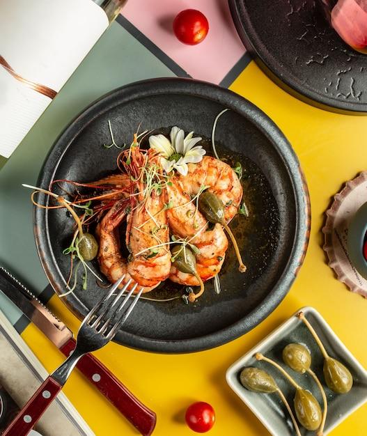 Vue de dessus de crevettes grillées garnies de cornichons et de fleurs Photo gratuit