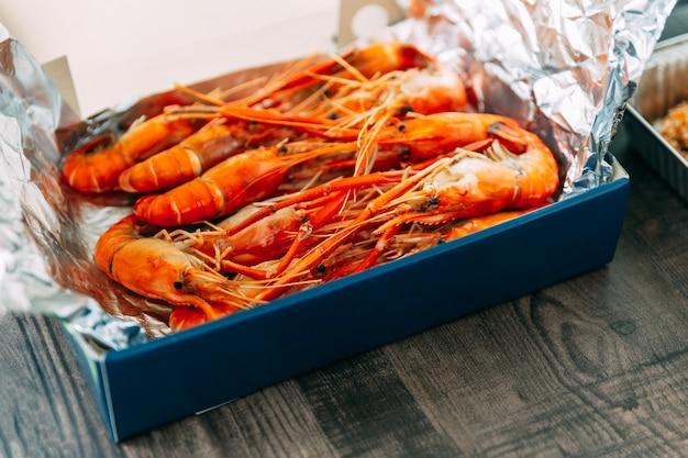 Vue de dessus des crevettes grillées thaïlandaises (crevettes) dans leur coquille dans une boîte en papier enveloppée de papier d'aluminium. Photo Premium