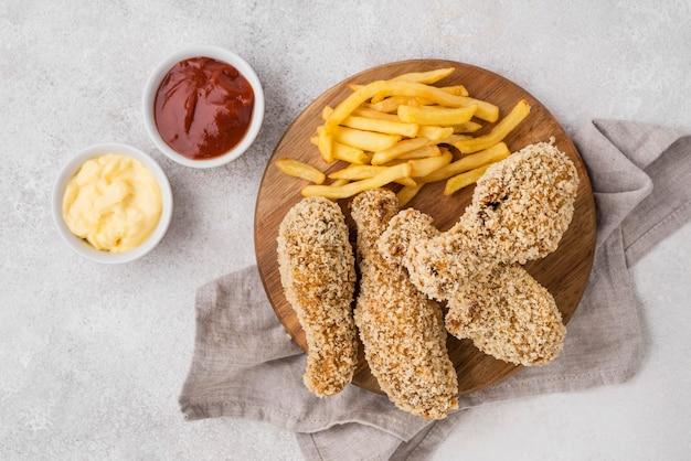 Vue De Dessus Des Cuisses De Poulet Frit Avec Des Sauces Et Des Frites Photo gratuit
