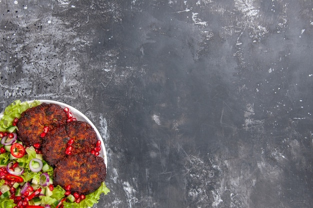 Vue De Dessus De Délicieuses Côtelettes De Viande Avec Salade Fraîche Photo gratuit