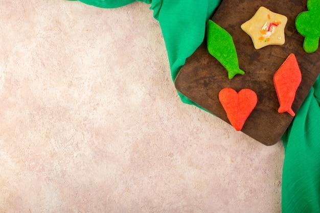 Vue De Dessus De Délicieux Biscuits Colorés Différents Formés Sur Le Bureau En Bois Brun Et Surface Rose Photo gratuit