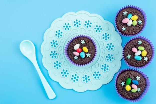 Une Vue De Dessus De Délicieux Brownies à L'intérieur Des Formes Violettes Avec Des Bonbons Colorés Sur Des Bonbons De Couleur Bleu, Bonbon Photo gratuit
