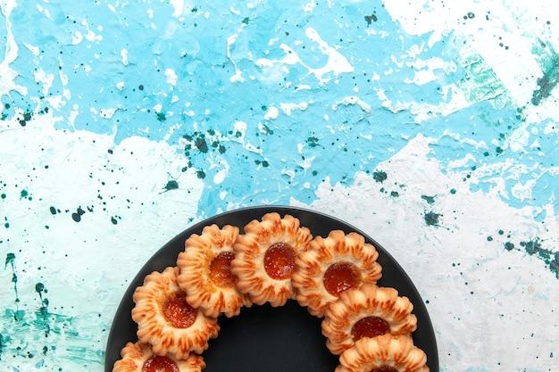 Vue De Dessus De Délicieux Cookies Rond Formé Avec De La Confiture à L'intérieur De La Plaque Noire Sur Fond Bleu Clair Cookie Biscuit Sucré Photo gratuit