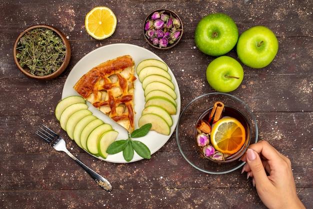 Une Vue De Dessus Délicieux Gâteau Aux Pommes Avec Du Thé Pommes Vertes Fraîches Et Citron Sur Le Sucre Biscuit Gâteau De Bureau En Bois Photo gratuit