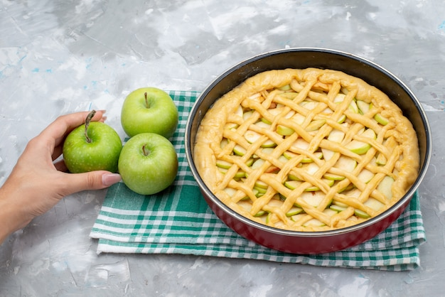 Une Vue De Dessus Délicieux Gâteau Aux Pommes Rond Formé à L'intérieur De La Casserole Avec Des Pommes Vertes Fraîches Sur Le Biscuit De Gâteau De Bureau Léger Photo gratuit