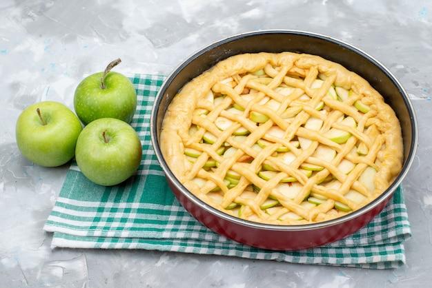 Une Vue De Dessus Délicieux Gâteau Aux Pommes Rond Formé à L'intérieur De La Casserole Avec Des Pommes Vertes Fraîches Sur Le Biscuit Gâteau Lumineux Bureau Photo gratuit