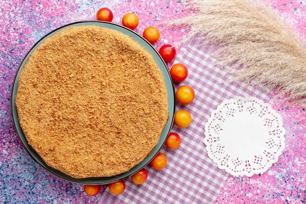 Vue De Dessus Délicieux Gâteau Rond à L'intérieur De La Plaque Avec Des Cerises-prunes Bordées Sur Le Bureau Rose Vif Gâteau Tarte Biscuit Sweet Bake Fruit Photo gratuit