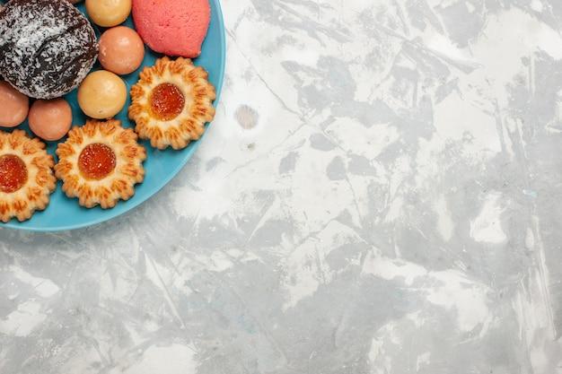Vue De Dessus De Délicieux Gâteaux Roses Avec Des Biscuits Et Un Gâteau Au Chocolat Sur Une Surface Blanche Photo gratuit