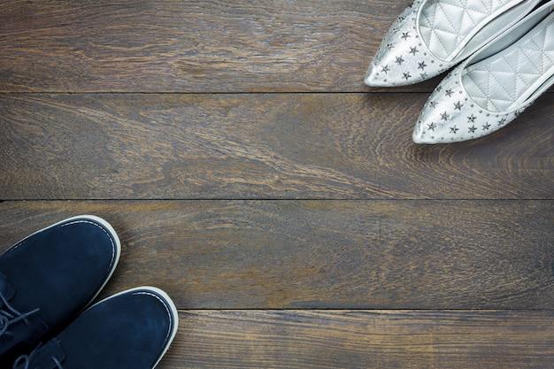 Vue de dessus design à la mode de chaussures hommes et femmes sur plancher en bois avec copie. Photo Premium