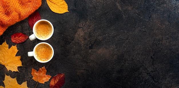Vue de dessus de deux tasses de café autour de feuilles jaunes Photo Premium