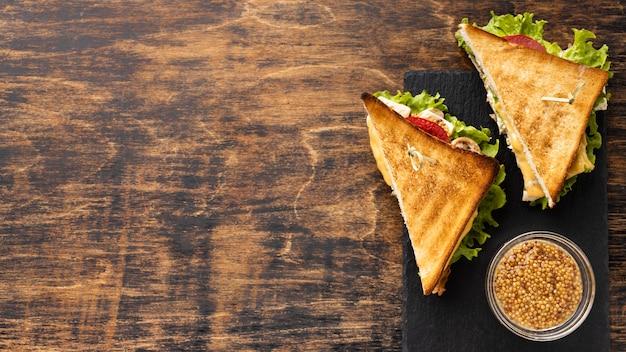 Vue De Dessus De Deux Tomates Triangulaires Et Sandwichs à La Salade Avec Espace De Copie Photo Premium