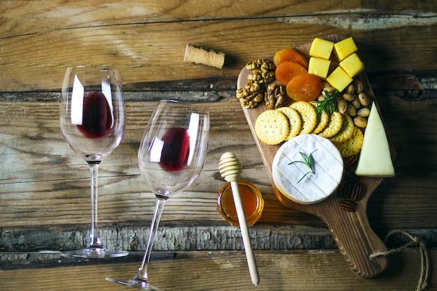 Vue de dessus deux verre de vin rouge et plateau de fromages Photo gratuit