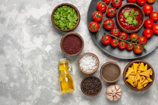 Vue De Dessus Différents Assaisonnements Avec Des Tomates Cerises Et De L'huile Sur Un Bureau Blanc Photo gratuit