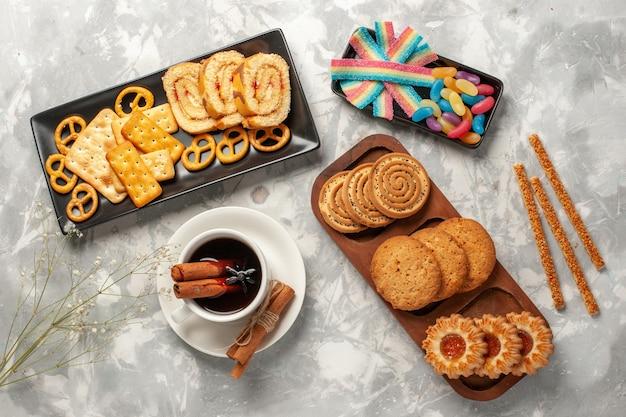Vue De Dessus Différents Cookies Avec Des Bonbons Et Une Tasse De Thé Sur La Surface Blanche Biscuits Biscuit Sucre Cuire Gâteau Tarte Sucrée Photo gratuit