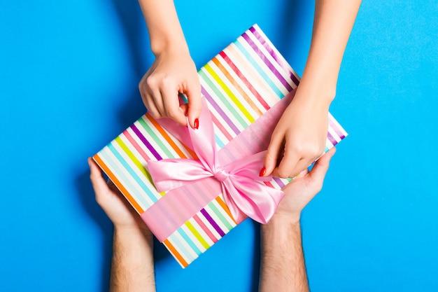 Vue De Dessus De Donner Un Cadeau à Une Belle Personne Sur Fond Coloré. Couple Se Féliciter. Concept Festif. Espace Copie Photo Premium