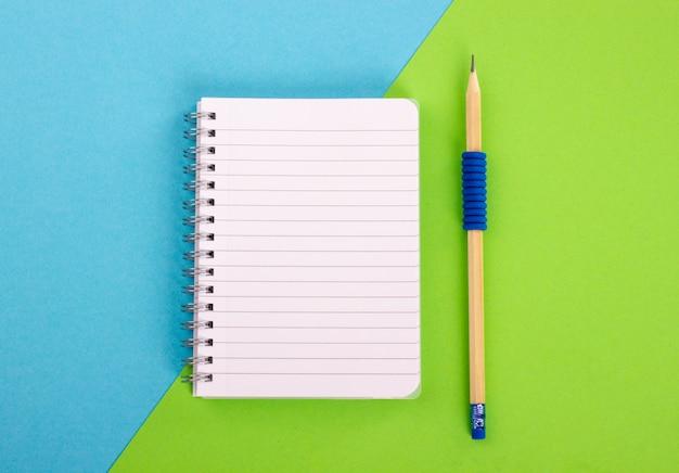 Vue de dessus du bloc-notes en spirale et un crayon en bois sur fond bleu-vert. style à plat Photo Premium