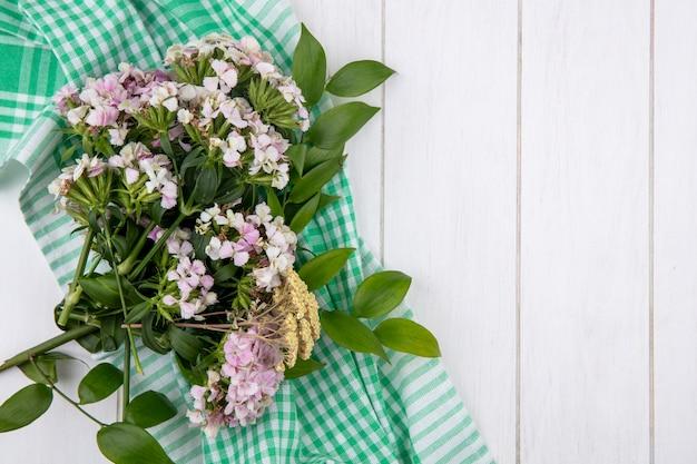 Vue De Dessus Du Bouquet De Fleurs Sauvages Sur Une Serviette à Carreaux Verts Sur Une Surface Blanche Photo gratuit