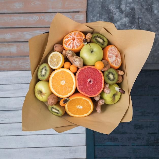 Vue de dessus du bouquet de fruits et de noix enveloppé dans du papier kraft Photo gratuit