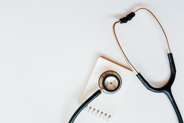 Vue de dessus du bureau moderne, stérile de médecins avec stéthoscope sur fond blanc. Photo Premium