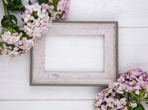 Vue De Dessus Du Cadre Blanc Avec Des Fleurs Sur Une Surface Blanche Photo gratuit